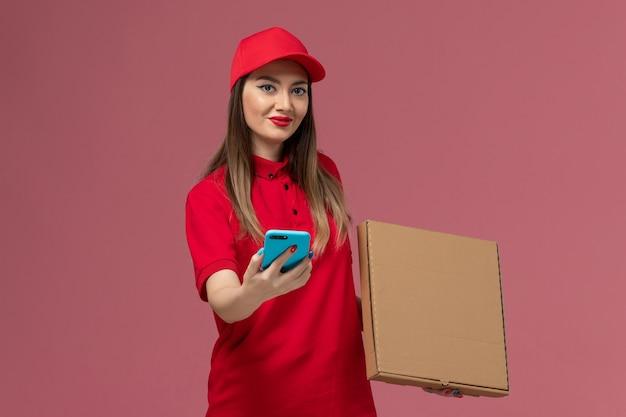 Junger weiblicher kurier der vorderansicht in der roten uniform, die lieferung-nahrungsmittelbox und telefon auf der rosa schreibtischdienstlieferuniform-arbeiterfirma hält