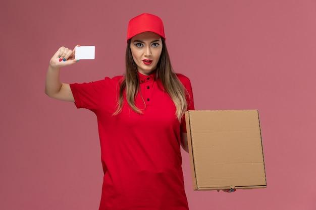 Junger weiblicher kurier der vorderansicht in der roten uniform, die lieferung-nahrungsmittelbox und weiße karte auf der rosa hintergrundlieferdienstuniformfirma hält
