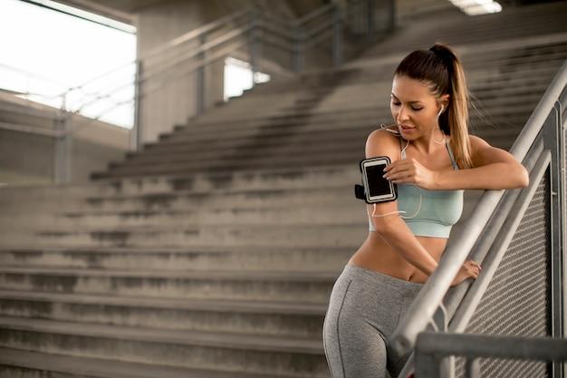 Junger weiblicher läufer, der auf treppen stillsteht