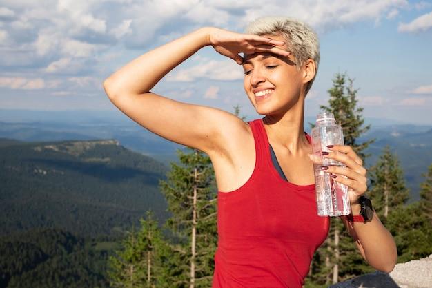 Junger weiblicher läufer, der eine flasche wasser hält