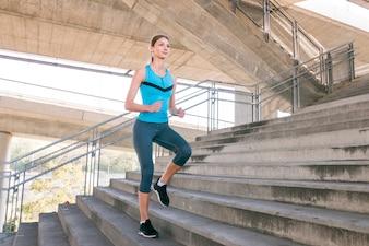 Junger weiblicher Läufer, der auf konkretem Treppenhaus rüttelt