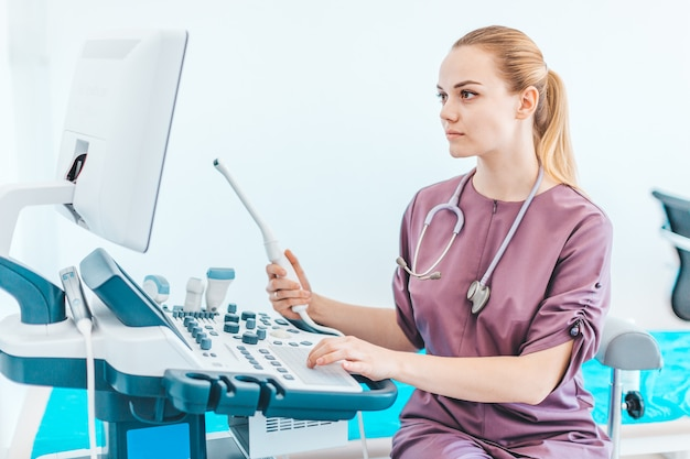 Junger weiblicher londe doktor mit schwarzen gläsern. ultraschallscanner in den händen eines doktors. diagnose. sonographie.