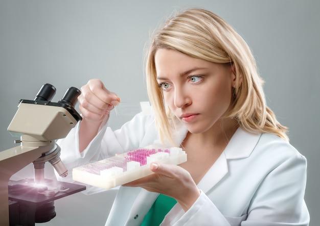 Junger weiblicher mikroskopiker im weißen mantel wählt eine gewebeprobe aus