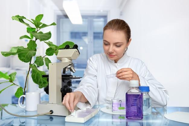 Junger weiblicher mikroskopiker im weißen mantel wählt eine gewebeprobe für microscopyspace aus