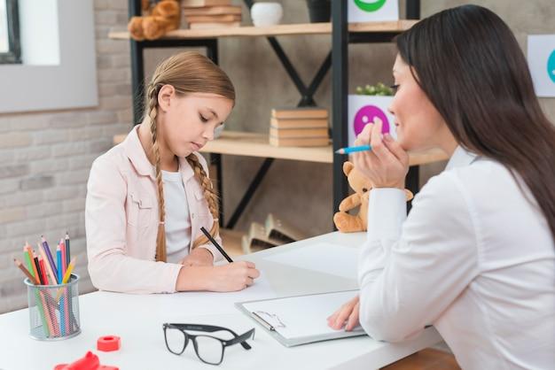 Junger weiblicher psychologe, die mädchenzeichnung auf papier über der tabelle beobachtend