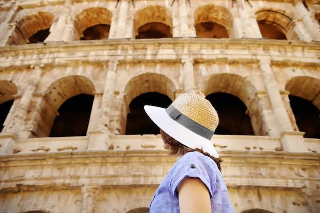 Junger weiblicher reisender, der auf berühmtem das colosseum in rom schaut.