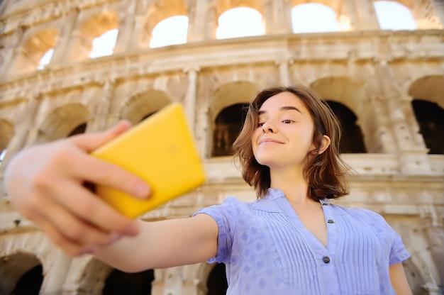 Junger weiblicher reisender, der das selfie foto steht das colosseum in rom, italien macht