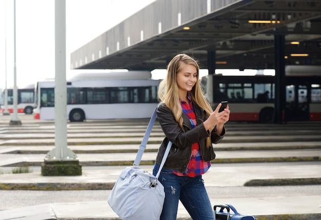 Junger weiblicher reisender, der handy betrachtet