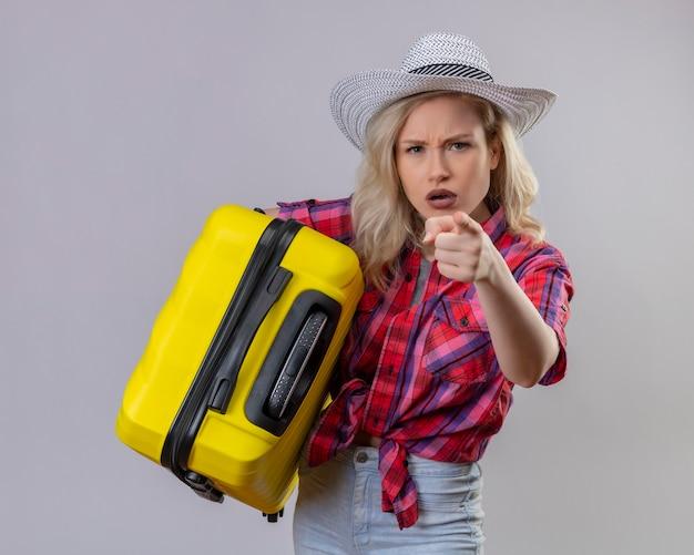 Junger weiblicher reisender, der rotes hemd im hut hält koffer trägt, der sie geste auf isolierter weißer wand zeigt