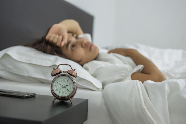 Junger weiblicher schlaf im schlafzimmer. schlaflosigkeit, sorgen und stress