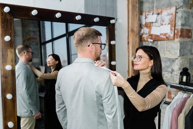 Junger weiblicher schneider, der maßnahmen der jacke des jungen mannes nimmt, während beide am spiegel in der werkstatt oder im modestudio stehen
