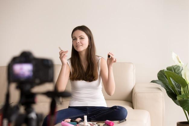 Junger weiblicher schönheitsblogger, der videobewertung macht