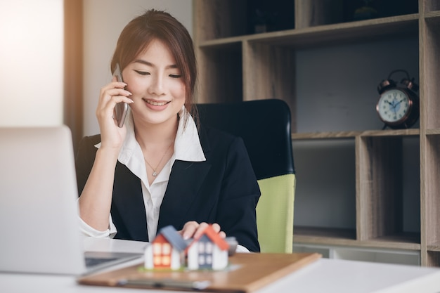 Junger weiblicher sekretär, der telefon für kontaktkundensitzungszeitplan hält