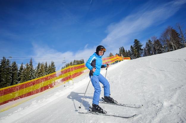 Junger weiblicher skifahrer an einem sonnigen tag am skiort