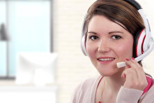 Junger weiblicher stütztelefonbetreiber im kopfhörer