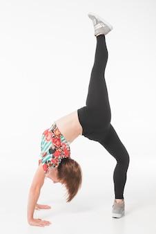 Junger weiblicher tänzer, der ihr bein oben ausdehnt
