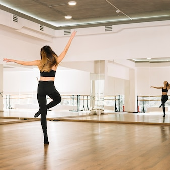 Junger weiblicher tänzer, der im tanzstudio übt