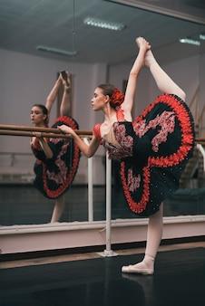 Junger weiblicher tänzer des klassischen balletts übend im tanzstudio