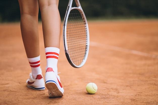 Junger weiblicher tennisspieler am gericht, füße nah oben