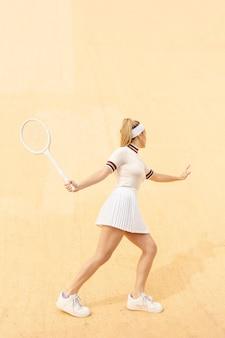 Junger weiblicher tennisspieler, der ball nachläuft