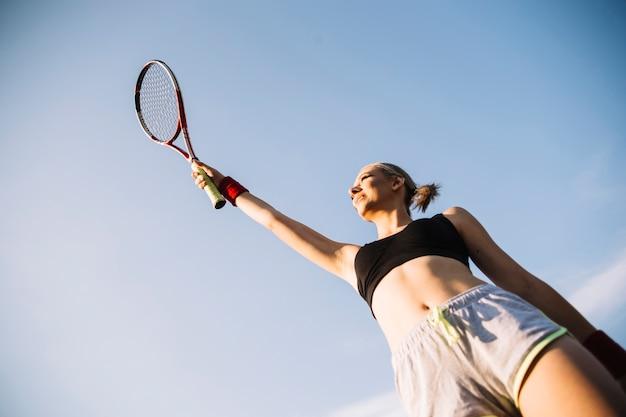 Junger weiblicher tennisspieler des niedrigen winkels, der schläger hält