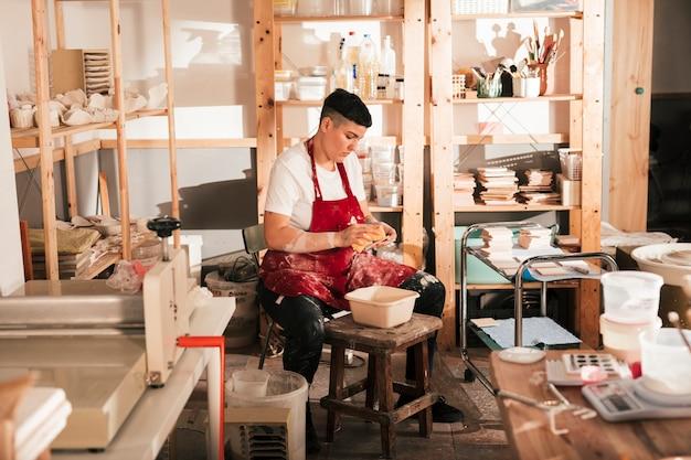 Junger weiblicher töpfer, der die keramikfliesen in der werkstatt säubert