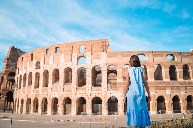 Junger weiblicher tourist, der das colosseum draußen in rom, italien betrachtet.