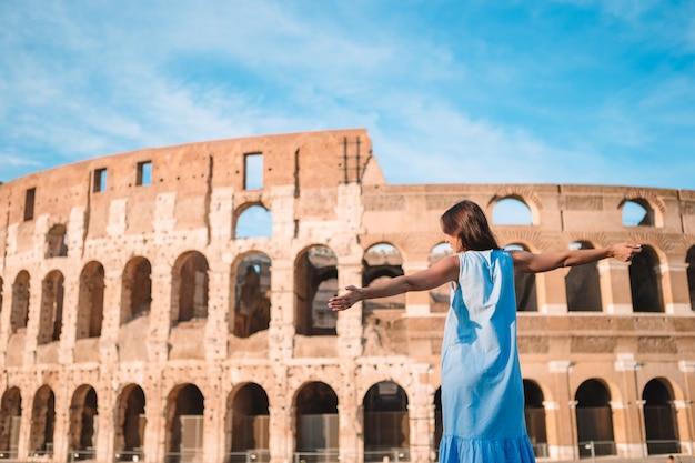 Junger weiblicher tourist, der das kolosseum außerhalb in rom, italien betrachtet.