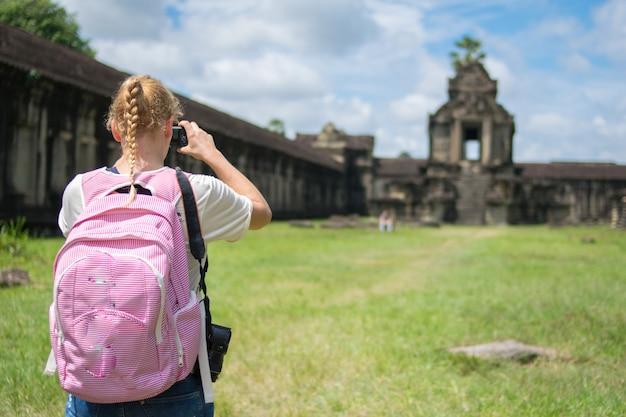 Junger weiblicher tourist mit dem smartphone, der foto von angkor wat tempel, kambodscha macht