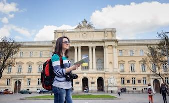 Junger weiblicher Tourist mit Karte und Kamera