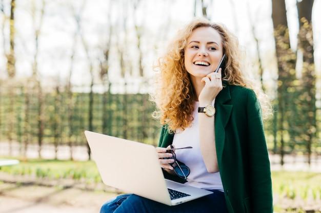 Junger weiblicher unternehmer mit dem flaumigen haar, das draußen vor der offenen generischen laptop-computer spricht am handy sitzt