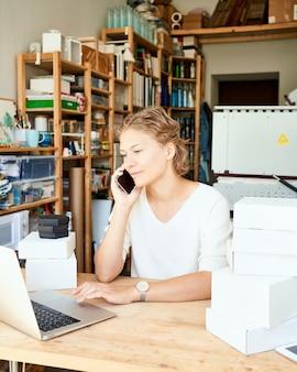 Junger weiblicher unternehmerdesigner, der auf handy spricht und laptop und lächelnde, glückliche dame im sonnigen tag in der werkstatt betrachtet. kleinunternehmen für frauen