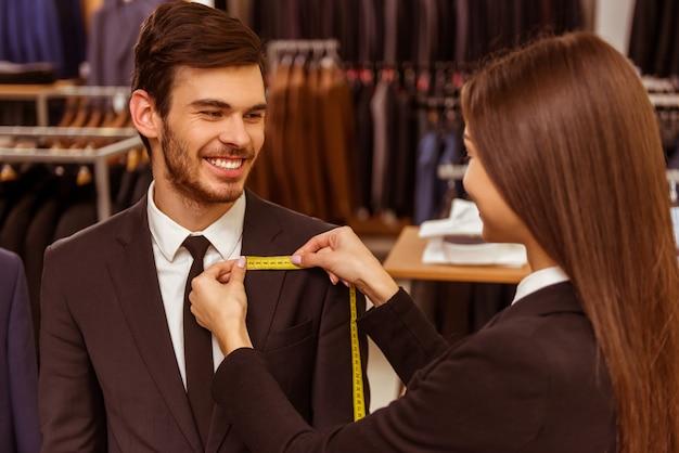 Junger weiblicher verkäufer, der maße eines mannes nimmt.
