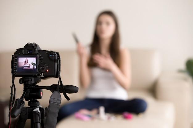Junger weiblicher videoblogger, der produktbewertung für blog aufzeichnet.