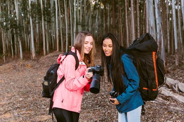 Junger weiblicher wanderer, der ihrem freund fotografie auf kamera zeigt