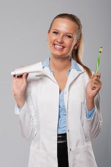 Junger weiblicher zahnarzt mit schönem lächeln, das zahnbürste und zahnpasta hält