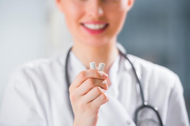Junger weiblicher zahnarztdoktor, der kaugummi und das lächeln hält