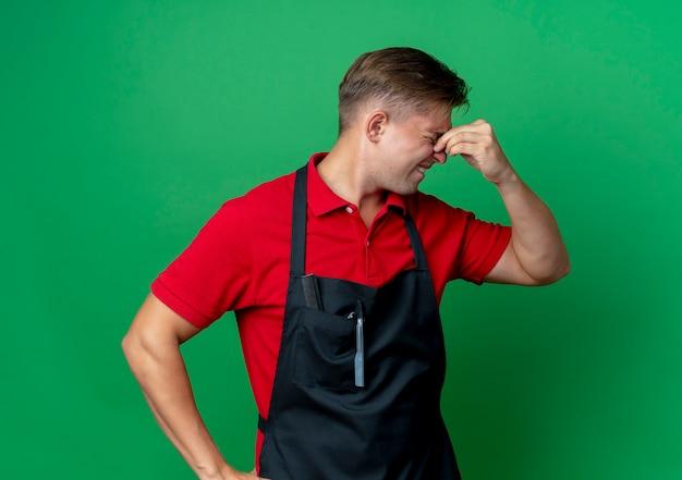 Junger weinender blonder männlicher friseur in uniform hält nase, die seite lokalisiert auf grünfläche mit kopienraum betrachtet
