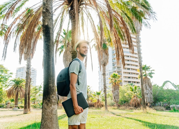 Junger weißer digitaler nomade, der in einem park mit einer stadt im hintergrund steht