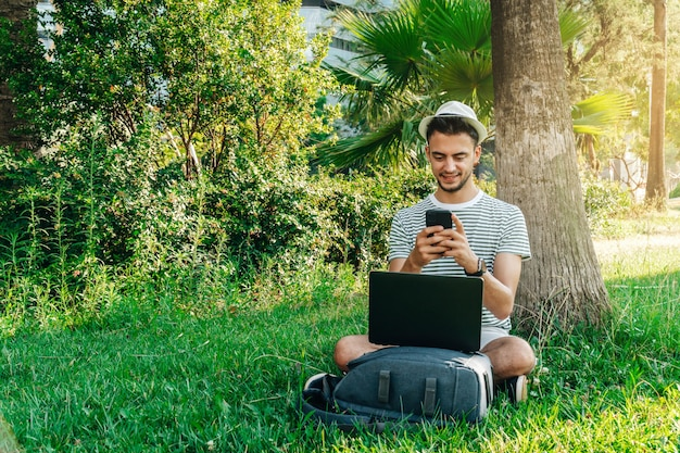 Junger weißer mann, der aus der ferne mit einem mobiltelefon arbeitet, das auf dem gras in einem park sitzt?