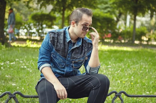 Junger weißer mann in der sonnenbrille sitzt im öffentlichen park.