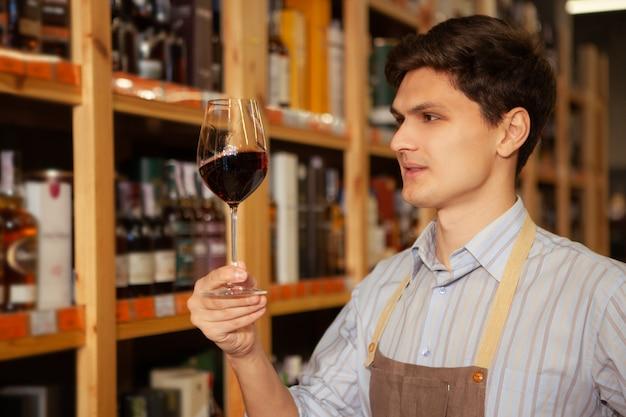 Junger winzer, der rotwein in seinem glas untersucht und in seiner eigenen weinhandlung arbeitet