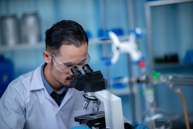 Junger wissenschaftler, der durch ein mikroskop in einem labor schaut. junger wissenschaftler forscht.
