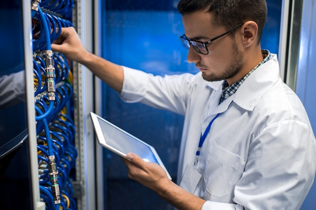 Junger wissenschaftler, der mit supercomputer arbeitet