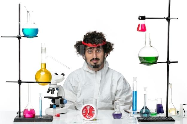 Junger wissenschaftler der vorderansicht im speziellen anzug, der speziellen schutzhelm auf weißem hintergrund trägt