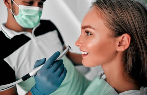 Junger zahnarzt, der zähne in einer zahnklinik an einer patientin mit geöffnetem mund arbeitet, untersucht und repariert. konzept für gesunde zähne.