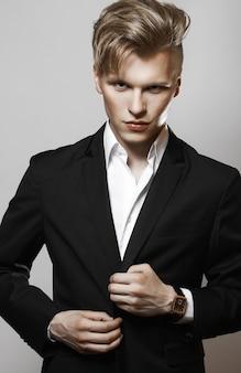Junger zauber gutaussehender mann im schwarzen anzug