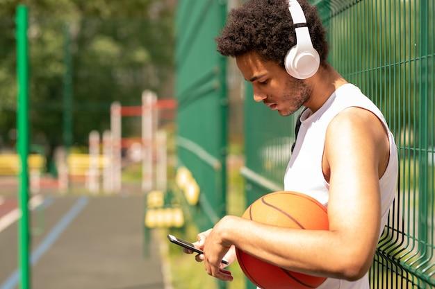 Junger zeitgenössischer basketballspieler in den kopfhörern, die durch zaun stehen, während in der pause in smartphone scrollen