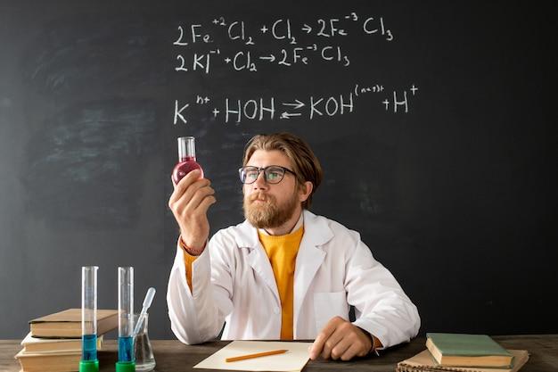 Junger zeitgenössischer chemielehrer im weißen kittel, der seine arme auf brust während der online-lektion kreuzt