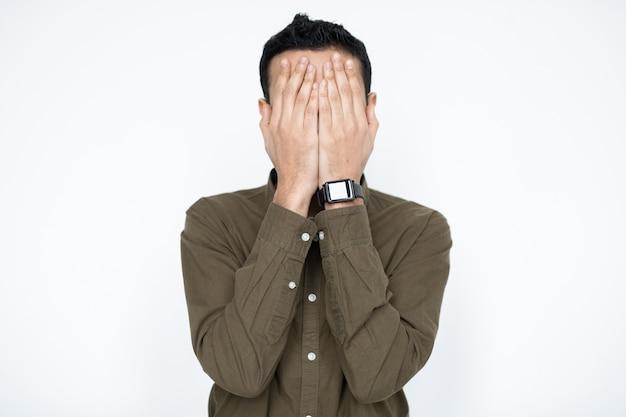 Junger zeitgenössischer geschäftsmann, der sein gesicht mit den händen bedeckt, während er versagen oder widerwillen isoliert ausdrückt